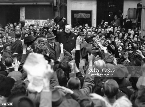British statesman Sir Winston Leonard Spencer Churchill raises his hat to the crowd at Walham Green during his tour of London