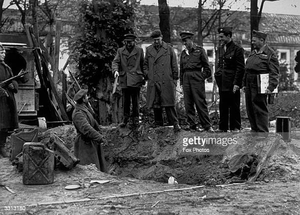 The alleged site of Adolf Hitler's grave behind the Chancellery in Berlin with soldiers standing alongside the petrol cans thought to have been used...