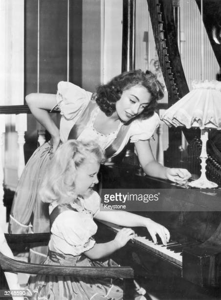 Hollywood actress Joan Crawford supervises her adoptive daughter Christina's piano practice Christina later acted and worked as Los Angeles...