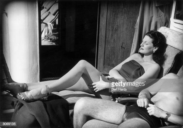 A couple of American passengers sunbathing on the deck of the transAtlantic liner Queen Elizabeth on their way to England Original Publication...