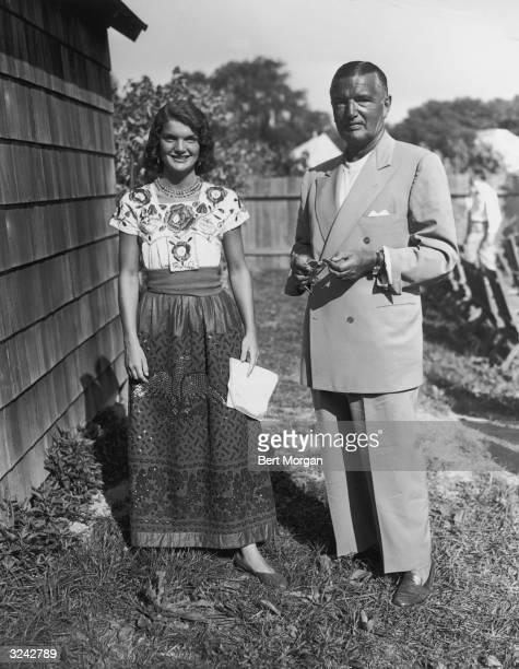 Full-length portrait of Jacqueline Bouvier , wearing a long, beaded skirt and embroidered blouse while standing beside a house or shed with her...