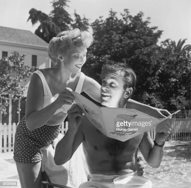EXCLUSIVE American actor Celeste Holm holding a tanning reflector under American actor Richard Carlson's face as the two relax at Carlson's Bel Air...