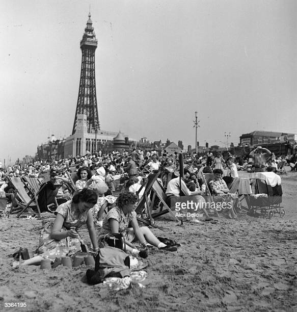 Holidaymakers on the beach at Blackpool during Wakes Week the annual holiday for workers in the industrial north Blackpool Tower can be seen in the...