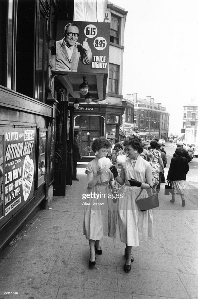 Twins from the Grogan family on holiday in Blackpool eating candy floss as they walk past a theatre where Arthur Askey is performing in 'Love And Kisses'. Original Publication: Picture Post - 8079 - Blackpool Wakes Week - unpub.