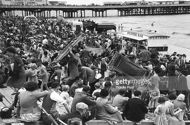A crowd of people on the beach at Blackpool some carrying deckchairs The pier is in the background Original Publication Picture Post 8944 Summer...