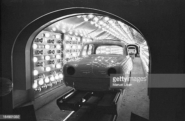 July 1957 visiting a factory RENAULT Here the body of the car passes under a tunnel with many lights perhaps the chain of drying paint on the body