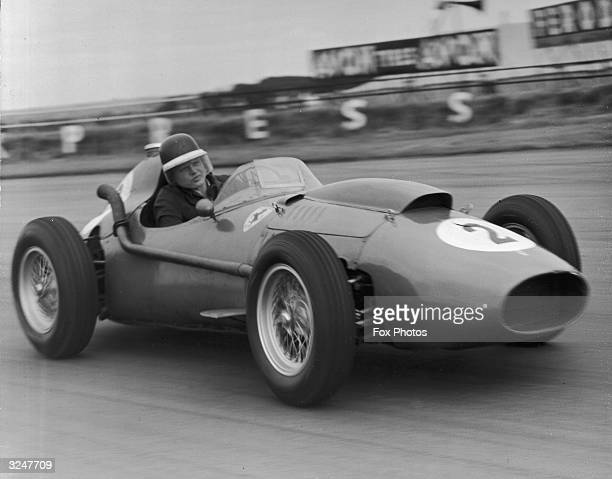 British racing driver Mike Hawthorn takes his Ferrari round a fast curve during practice for the British Grand Prix at Siverstone.