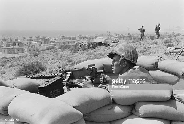 July 1958 US Marine sits in a foxhole and points a machine gun towards Beirut Lebanon in the distance