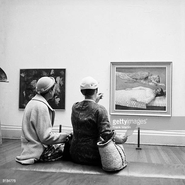Visitors evaluate a painting at an exhibition of modern art organised by the Contemporary Art Society on the theme of religion in London's Tate...