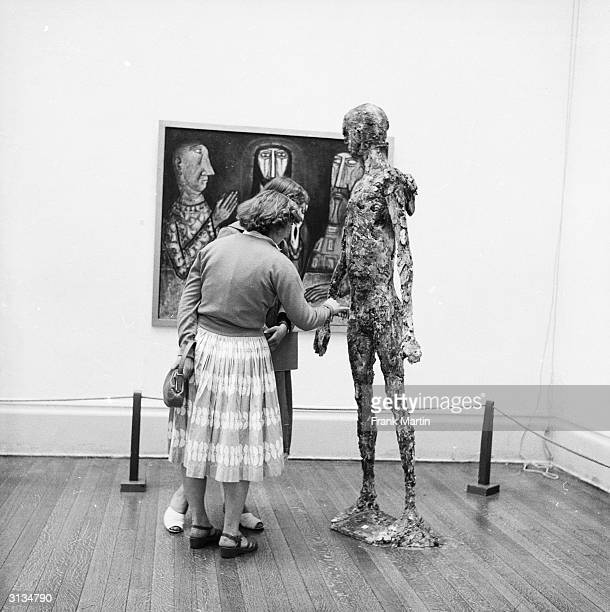 Visitors examine a plaster figure of Saint Michael at an exhibition of modern art organised by the Contemporary Art Society on the theme of religion...