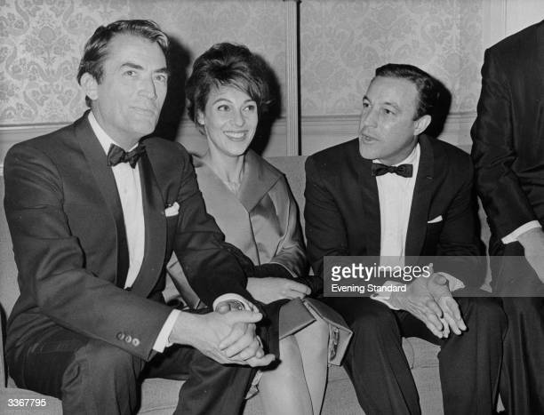 American screen star Gregory Peck and his wife Veronique sit with dancer and actor Gene Kelly at the Astoria, London.
