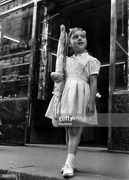 A young girl with two baguettes which she has just bought from a bakery in Paris