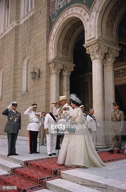 King Paul I of Greece, wearing military uniform, leaves an official function with Queen Frederika.