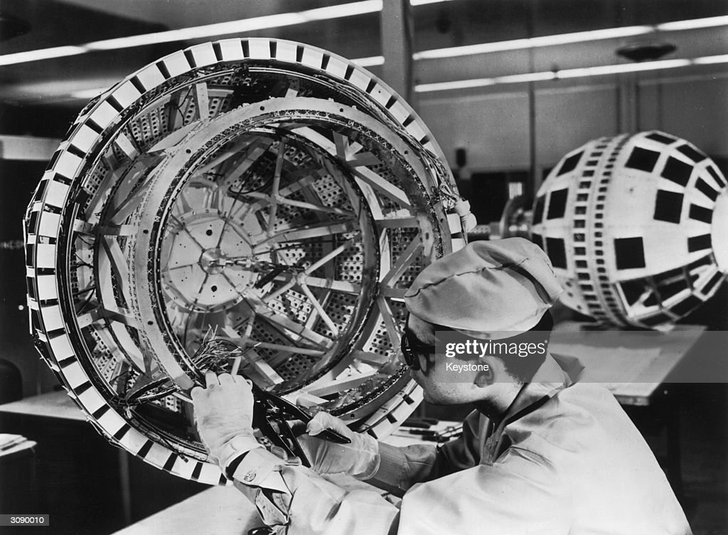 A technician prepares to wire together the components of the Bell System's Telstar experimental communications satellite, shortly before its launch into orbit. Telstar was the first satellite to relay television programmes between Europe and the United States.