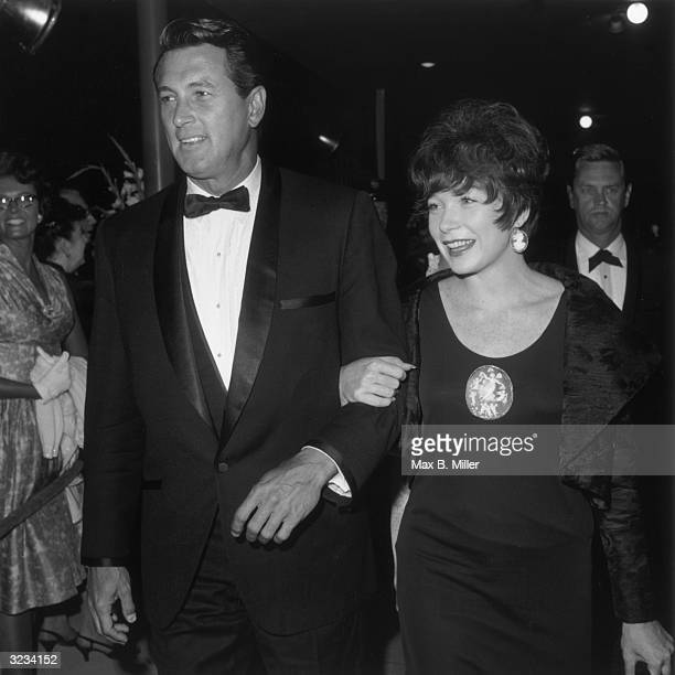 American actors Rock Hudson and Shirley MacLaine smiling and walking arminarm at the premiere for director William Wyler's film 'How to Steal a...