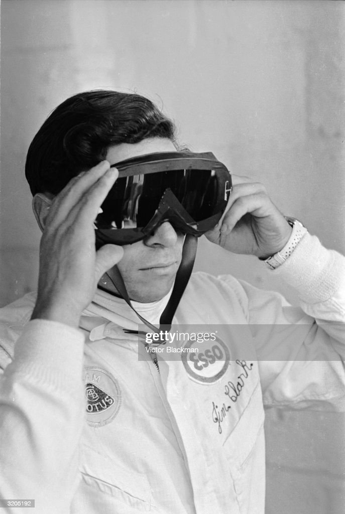 British racing driver Jim Clark (1936 - 1968), watching the qualifying rounds for the British Grand Prix from the Lotus pits at Brands Hatch.