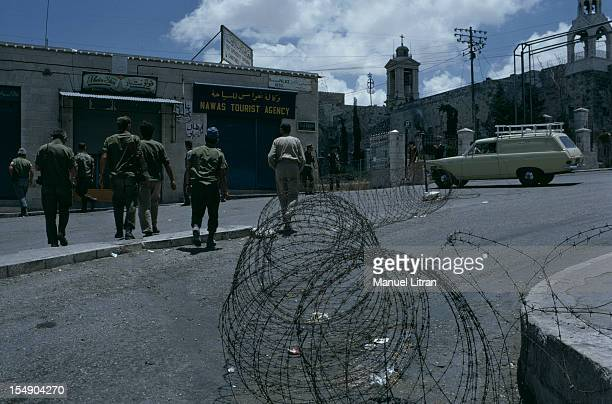 July 1967 after the 'Six Day War' Israel tripled its surface area Israeli soldiers patrol in a city In the foreground a roll of barbed wire blocked...