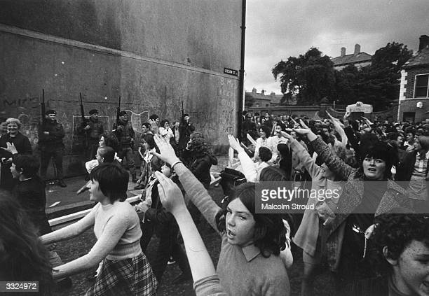 A crowd of demonstrators passing British soldiers in Leeson St in the Falls Road area of Belfast
