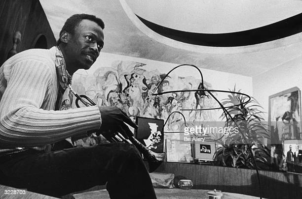 American jazz musician Miles Davis holds a trumpet as he sits on the back of a rounded sofa in his platformed curvilinear living room decorated by...