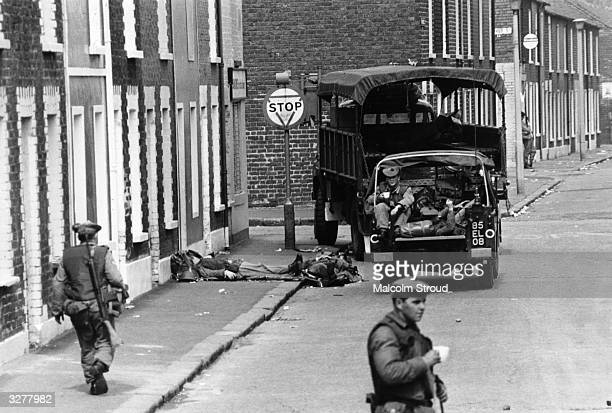 Armed British soldiers impose a curfew on the Falls Road in Belfast.