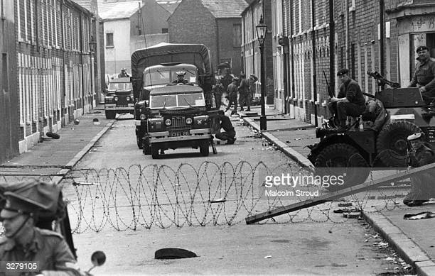 Armed British soldiers impose a curfew on the Falls Road in Belfast