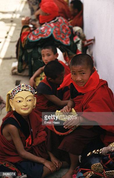 Red robed boy priests one wearing a mask are getting ready for a ceremonial dance during the coronation ceremony of King Jigme Singye Wangchuk of...