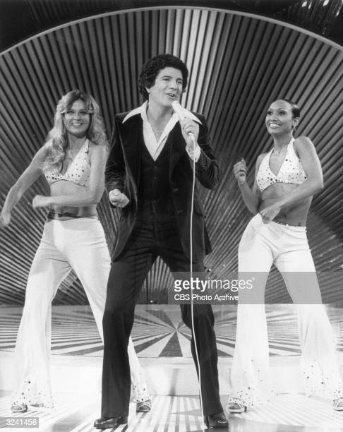 Fulllength promotional photo of American actor singer dancer and game show host Bert Convy singing and dancing on a stage with two female dancers on...