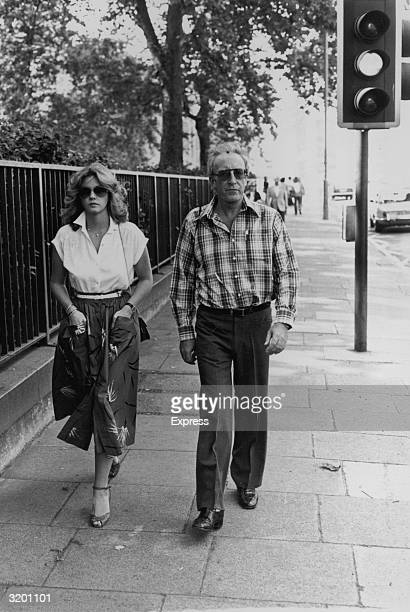 Fulllength image of British actor and comedian Peter Sellers and his wife British actor Lynne Frederick walking down the street in London England