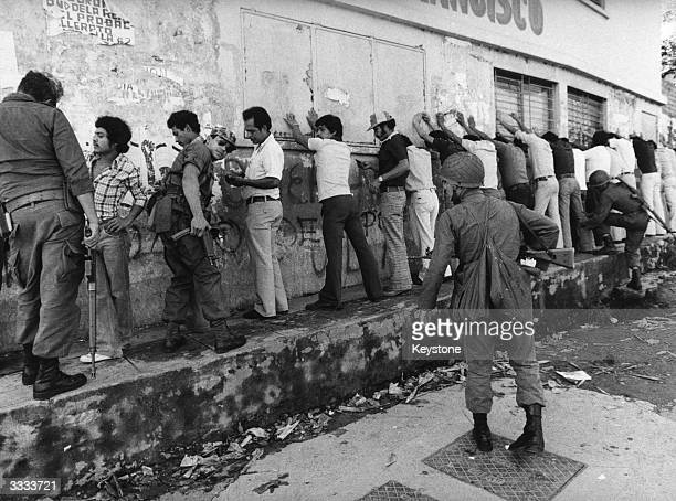Young people many of them students being lined up against a wall and searched by members of the El Salvadorean Army during unrest in the capital San...