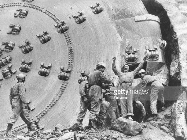 The construction driving team celebrate reaching the end of their work In the background is the enormous tunneldigger which allowed them to dig ten...