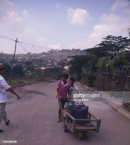 July 1988]: MANDATORY CREDIT Bill Tompkins/Getty Images Children pushing a cart with water containers. The Payatas Dumpsite, a 13 hectare garbage...