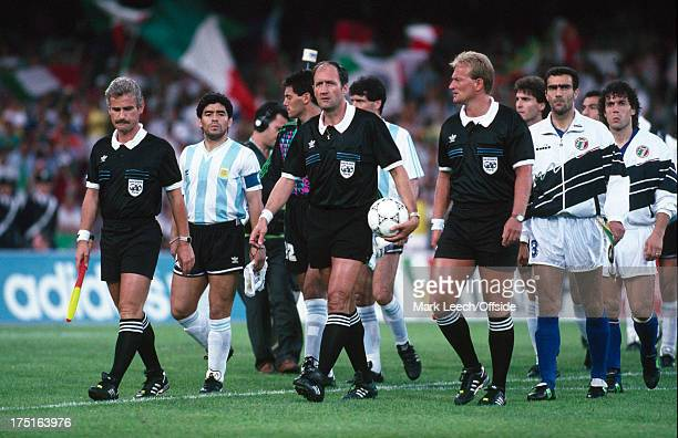 July 1990 World Cup Football semi-final - Argentina v Italy - Referee Michel Vautrot carries the matchball as he and his assistants lead out the two...