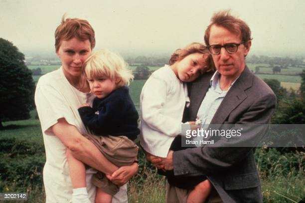 American actor Mia Farrow and her partner American film director writer and actor Woody Allen hold their children Satchel and Dylan on a hill top...