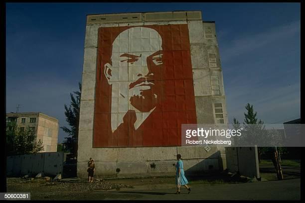 Street wall mural of Lenin towering above passersby in formerly Soviet Central Steppes region city Ekibastuz