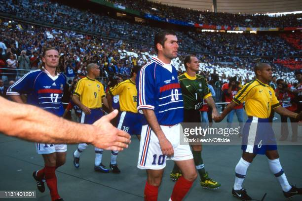 July 1998 - FIFA World Cup - Final - Stade de France - Brazil v France - Zinedine Zidane of France walks past a fans out streched hand on his way to...