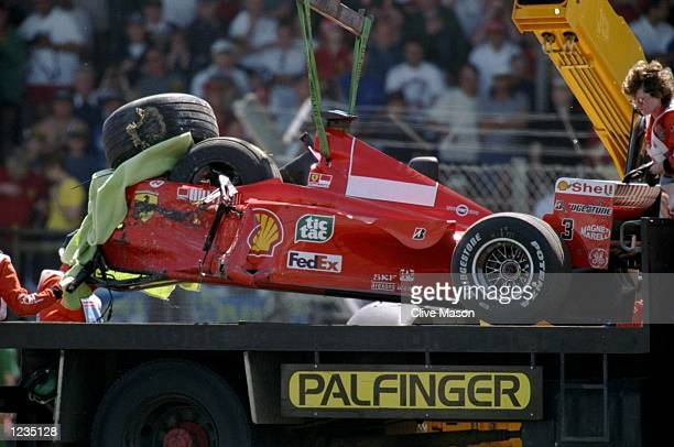 Michael Schumachers's Ferrari is loaded onto a recovery vehicle crashing into a barrier as a result of brake failure at the 1999 Formula One British...