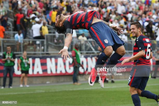 Dom Dwyer of the United States celebrates scoring on debut with a back flip watched by team mate Kelyn Rowe of the United States during the United...