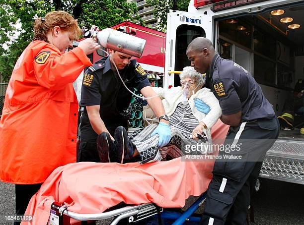 July 20 2008 An unidentified elderly woman is given oxygen while being helped on a stretcher by Toronto EMS oustide an apartment fire on Secord...