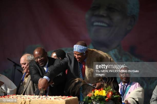 Deputy president Kgalema Motlanthe Chief Mandla Mandela Mathole Motshekga and Denis Goldberg cut Nelson Mandela's birthday cake while the crowd sang...
