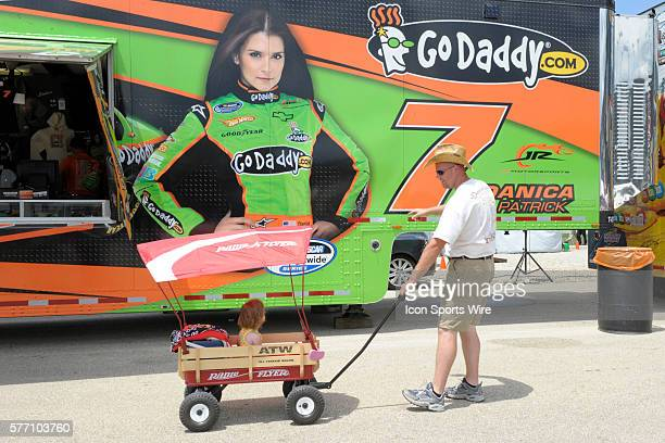 A father and daughter check out the image of Danica Patrick on Patrick's merchandise trailer on the midway of the ChicagoLand Speedway prior to the...
