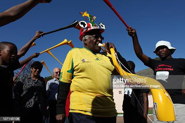 Archbishop Desmond Tutu attends a roof wetting ceremony in Masiphumelele Wearing his Bafana Bafana outfit with his makarapa the Archbishop urged...