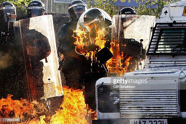 A police officer is engulfed in flames during rioting at Ardoyne Belfast where around 200 youths threw petrol bombs and bricks Picture Cliff Donaldson