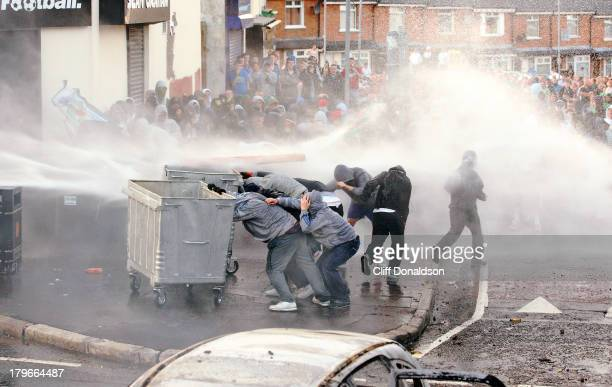 Rioters take shelter behind waste bins as police deploy a water cannon during disturbances at Ardoyne Belfast where around 200 youths threw petrol...