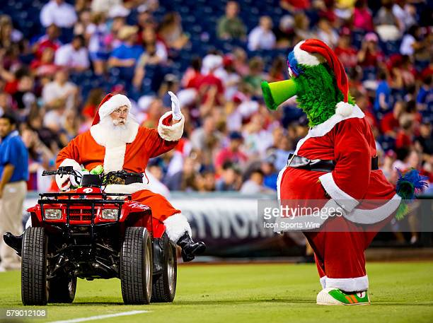 Celebrating Christmas in July Santa joins the Phillie Phanatic on the field during the fifth inning break during a Major League Baseball game between...