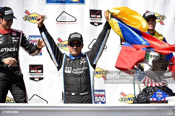 Juan Pablo Montoya celebrates in victory lane with Helio Castroneves and Carlos Munoz after wining the Pocono 500 at Pocono Raceway in Long Pond PA
