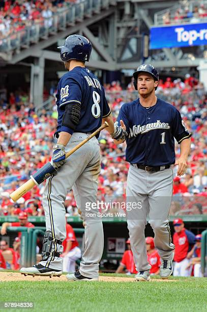 Milwaukee Brewers left fielder Logan Schafer scores and is congratulated by right fielder Ryan Braun at Nationals Park in Washington DC where the...