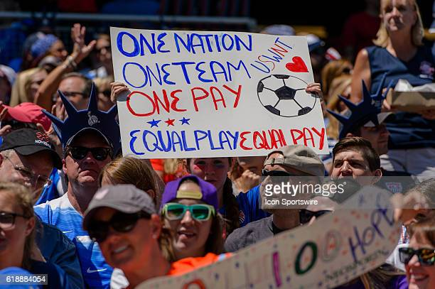 A fan holds and equal play equal pay sign during an international friendly soccer match between South Africa and USA at Soldier Field in Chicago IL...