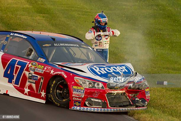 AJ Allmendinger pulls off his gloves after a crash during the NASCAR Sprint Cup Series Quaker State 400 at Kentucky Speedway in Sparta KY