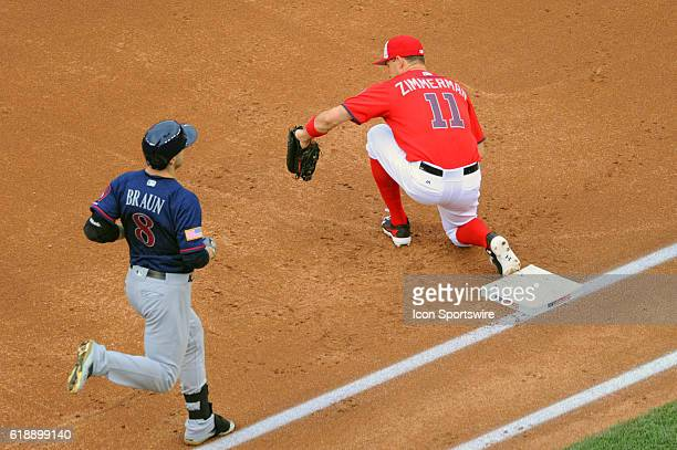 Washington Nationals first baseman Ryan Zimmerman reaches to catch a throw to retire Milwaukee Brewers left fielder Ryan Braun at Nationals Park in...