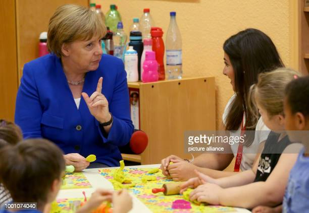 German chancellor Angela Merkel visits the Caritas Centre Kalk and accompanies children during their creative selfexpression Photo Oliver Berg/dpa